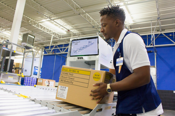 Walmart associate Tanaka uses the new FAST Unloader to unload boxes