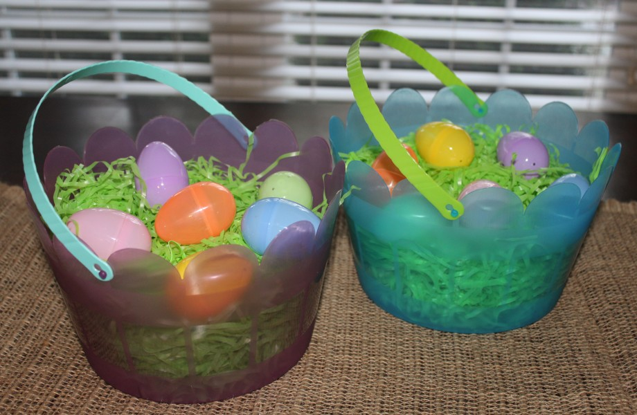 Two Easter baskets sit on a table with plastic eggs inside them