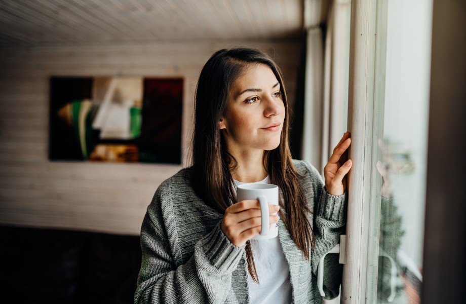 Woman with Coffee Mug Looking Out Window