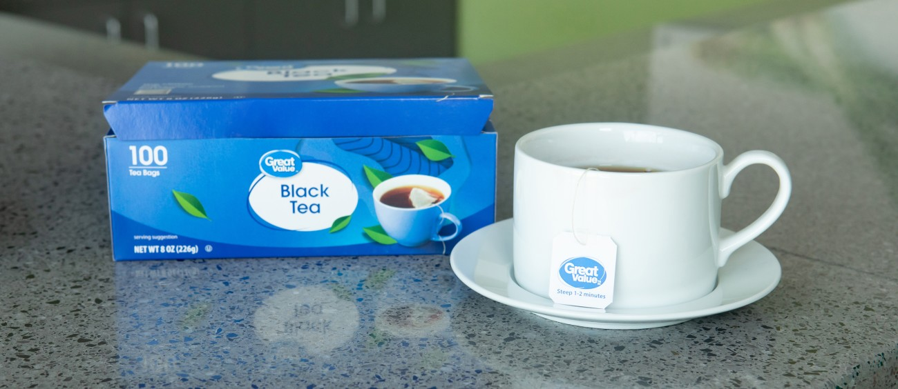 A cup and box of Great Value tea on a kitchen counter