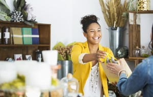 Small business worker hands a purchase to a customer