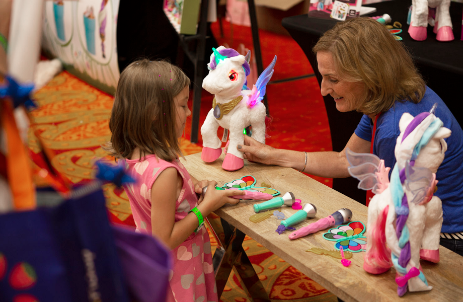 Child testing unicorn toy at Top Rated by Kids event