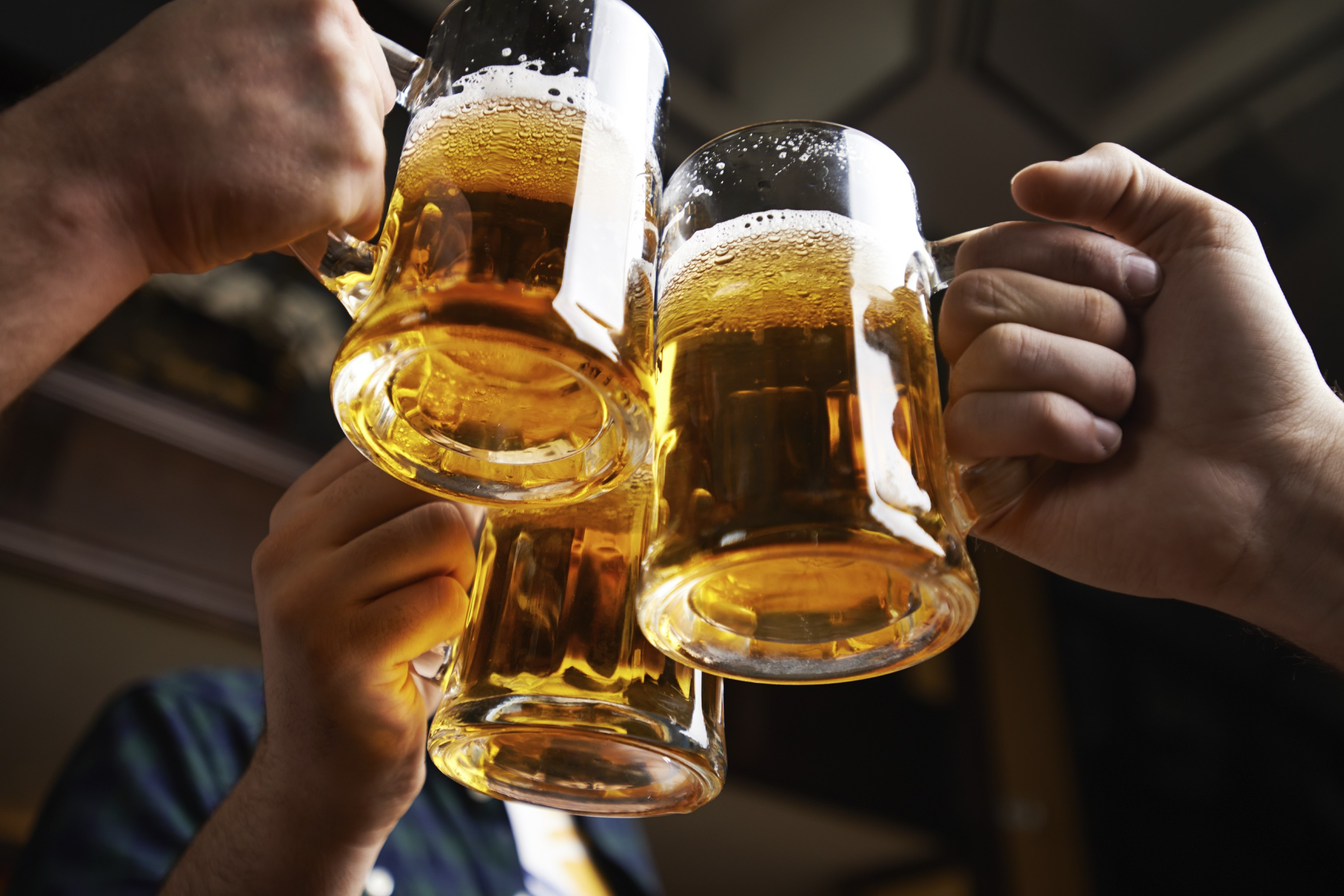 Three beer mugs are held together for a 'cheers'