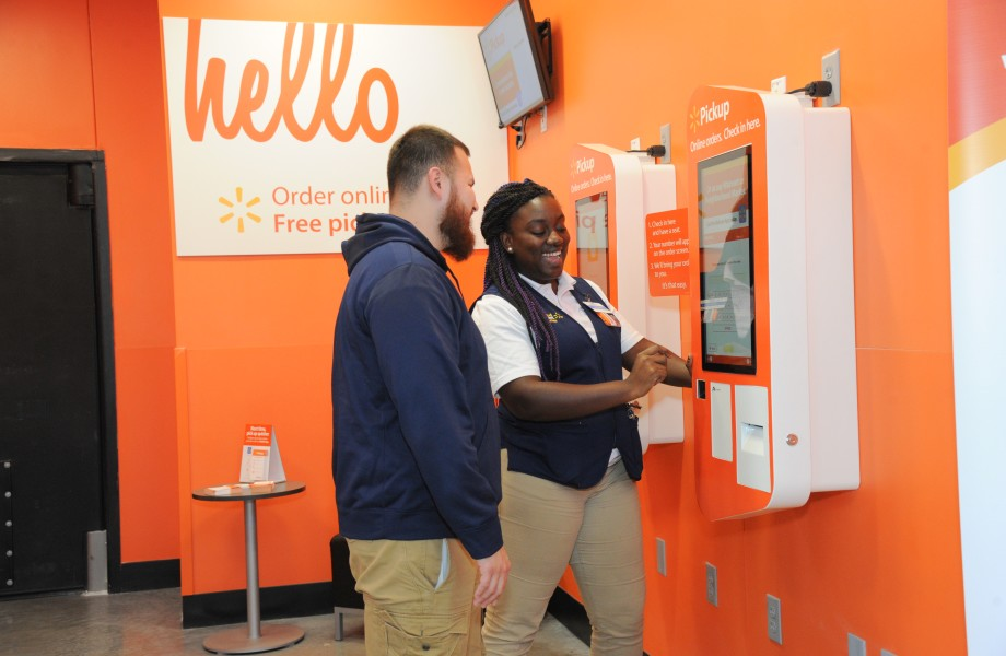 Associate at pick up kiosk helps customer with his order
