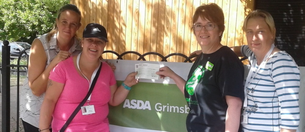 Asda Grimsby community champion Lynn Bailey presenting a cheque