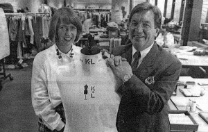 A nicely dressed man and a woman smile while standing near a clothing mannequin