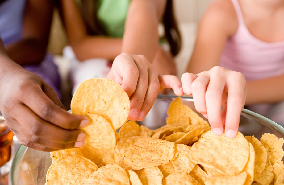 Three young girls reach in to a snack bowl filled with chips