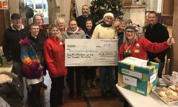 Asda Pwllheli community champion Jo Scott presenting the group with their surprise Christmas cheque