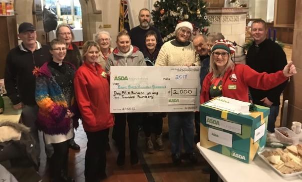 Asda Pwllheli community champion Jo Scott presenting the group with their surprise Christmas cheque