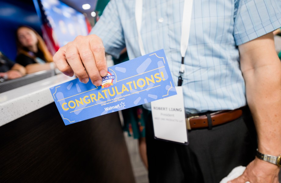 A supplier holds a 'Congratulations' ticket at the 2018 Open Call for U.S. Manufacturers in Bentonville, Ark.