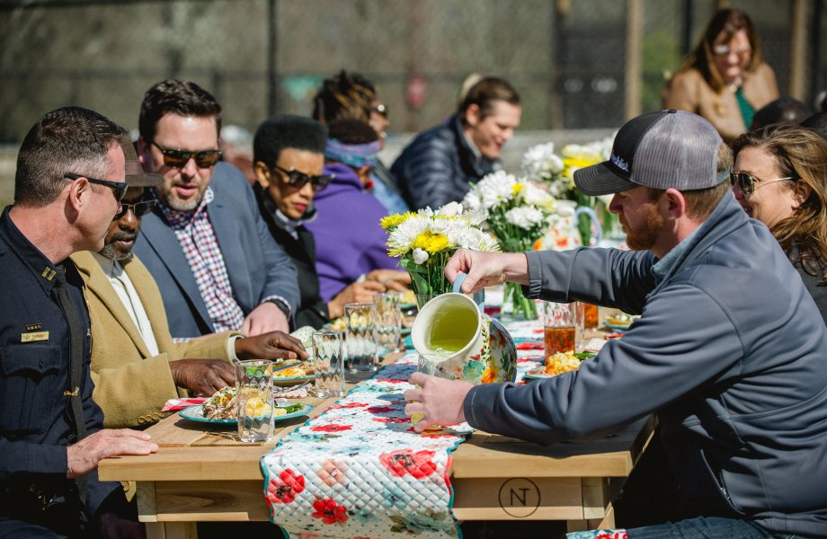 Members of the community share a meal in Charlotte, N.C. on handcrafted tables made by Neighbor's Table