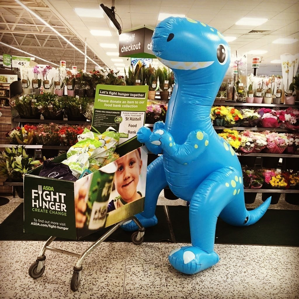 Our full foodbank trolley being guarded by the inflatable dinosaur 🦖 | Asda St Austell