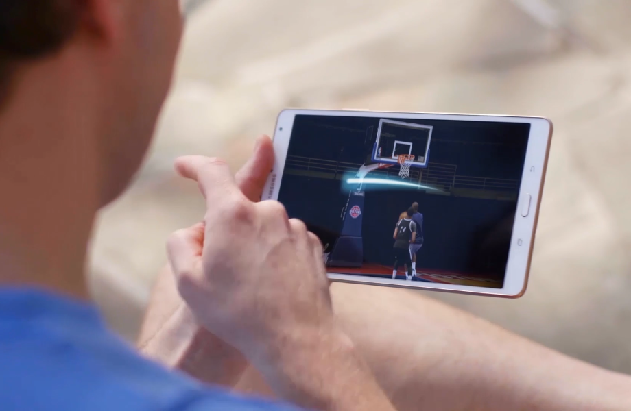 A man plays a basketball game on a tablet