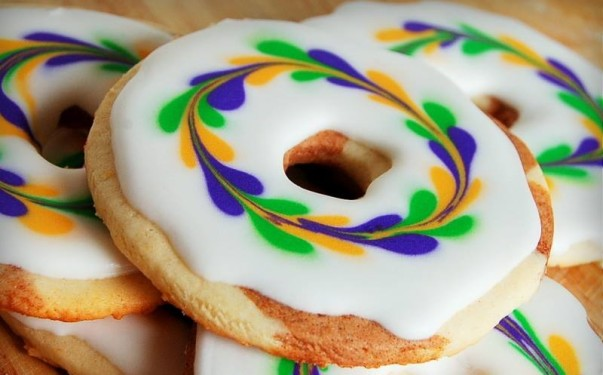 A small stack of king cake cookies have bright yellow, purple and green swirled icing