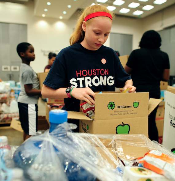 A young girl helping pack supplies for hurricane relief in a Houston Strong t-shirt