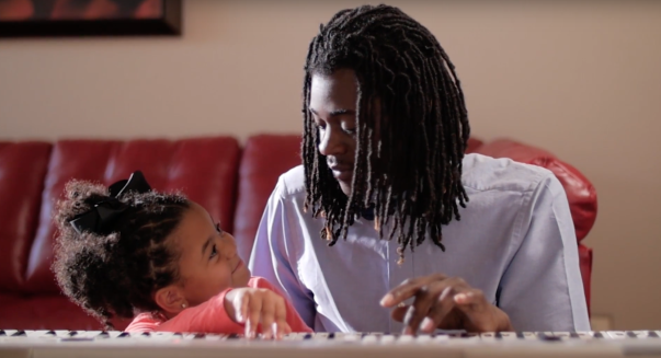 A man and his young daughter play piano together