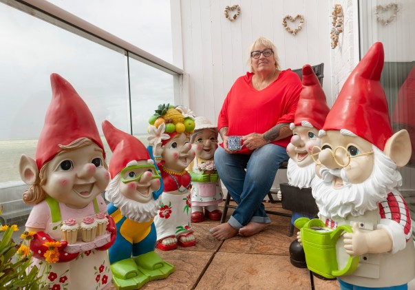 Janet Wilson on her balcony with a collection of 40 Asda gnomes