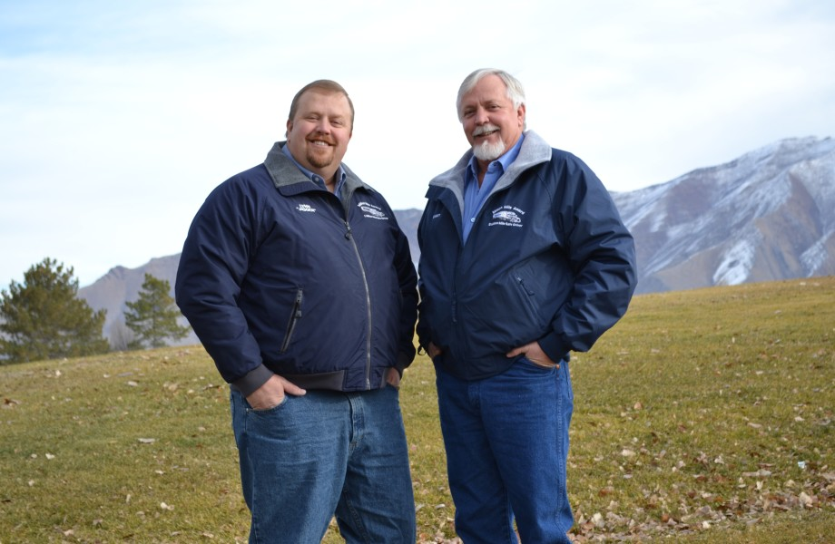 Truck drivers, Lynn Halterman and Wyatt Jepsen, stand beside each other in front of mountains in the distance