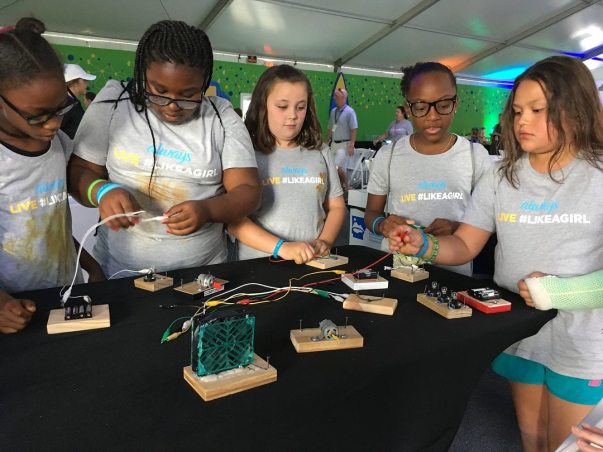 A group of girls tinker with electronics at the Always Live #LikeAGirl STEAM Day
