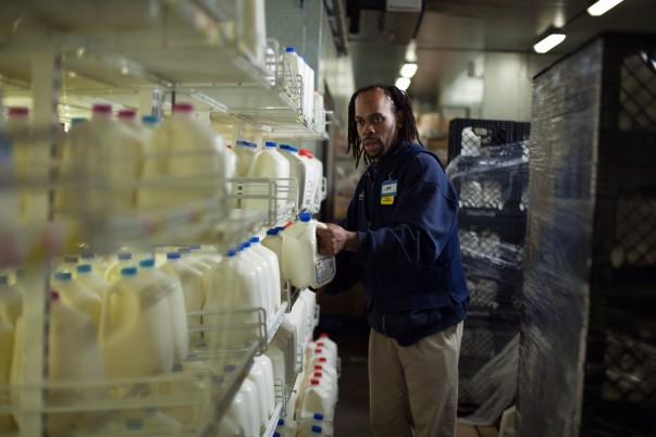 John Geeter grabs a gallon of milk from a shelf in a Walmart dairy department back room
