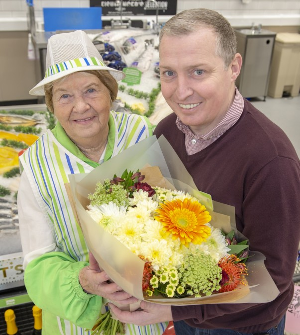 Jason Clark from Asda Carlisle gives Freda Mounsey a bunch of flowers for her 80th birthday