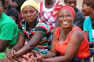 Women farmers smile at the camera.