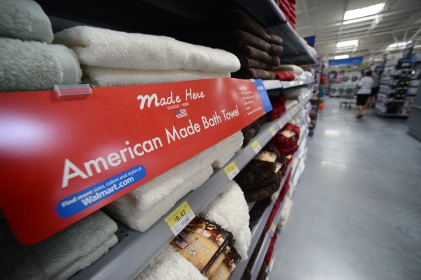 "A ""Made in America"" sign is in front of bath towels on a shelf"