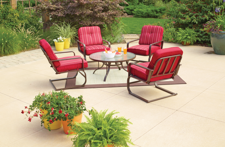 Four metal chairs with red cushions are gathered together around a rectangular glass table on an outdoor concrete patio.