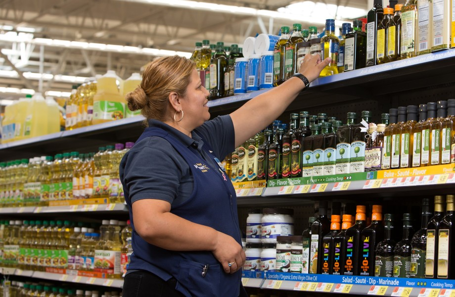 Associate stocking grocery items on the top shelf