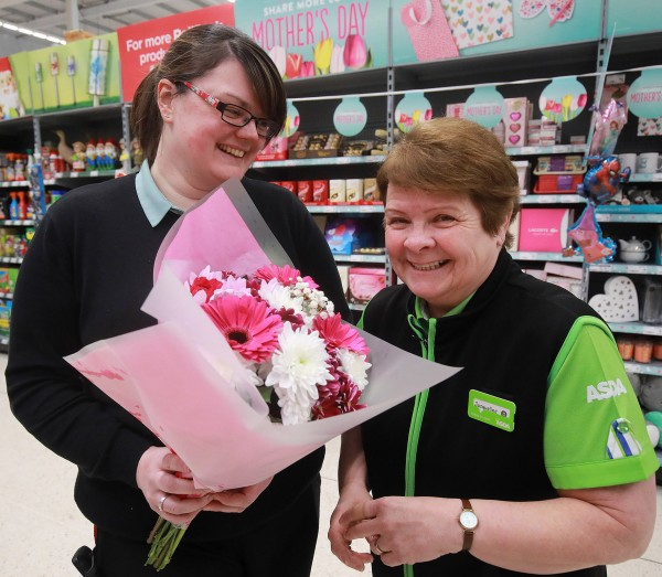 Rachelle presenting Jacqui (right) with flowers to mark Mother's Day at Asda Larne
