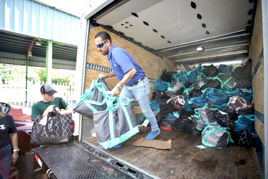 Associate volunteering in Puerto Rico giving bags of donations away
