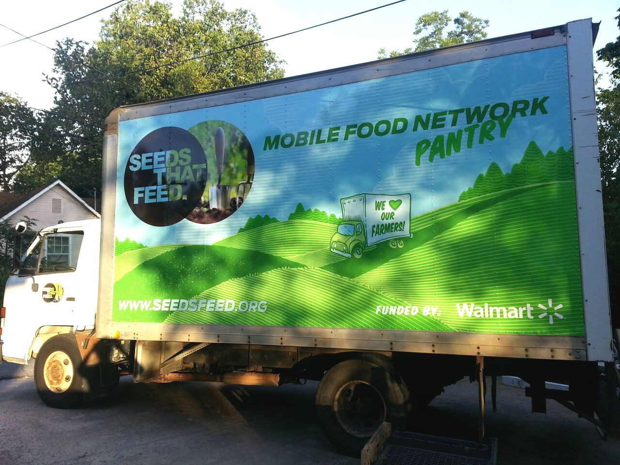 A large white box truck with the Seeds that Feed logo is parked on the road.