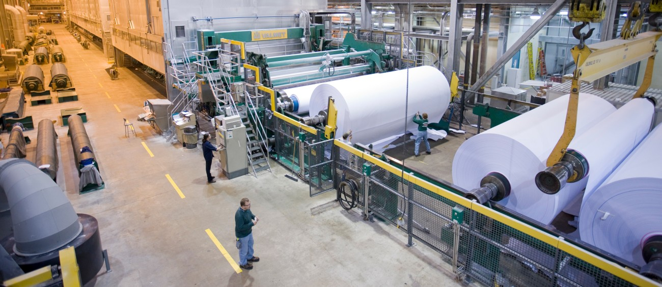 Employees work inside a paper mill