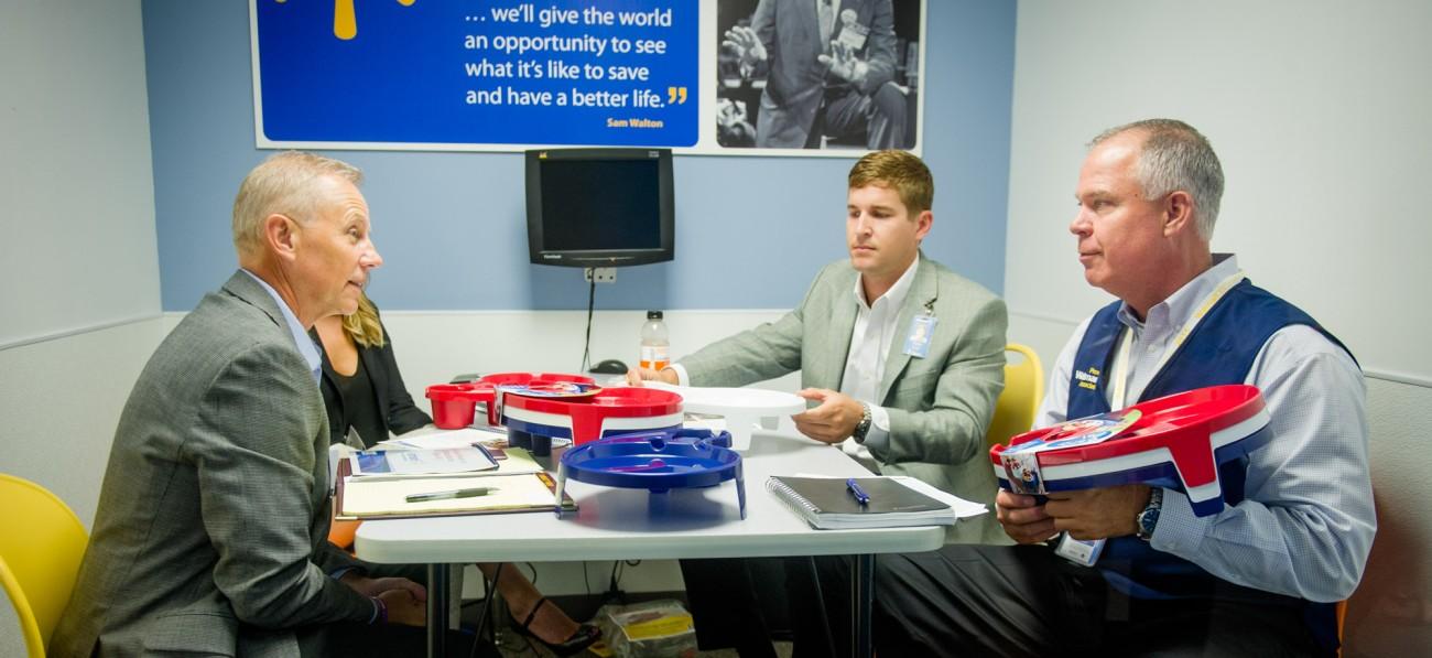 A potential supplier meets with Walmart associates