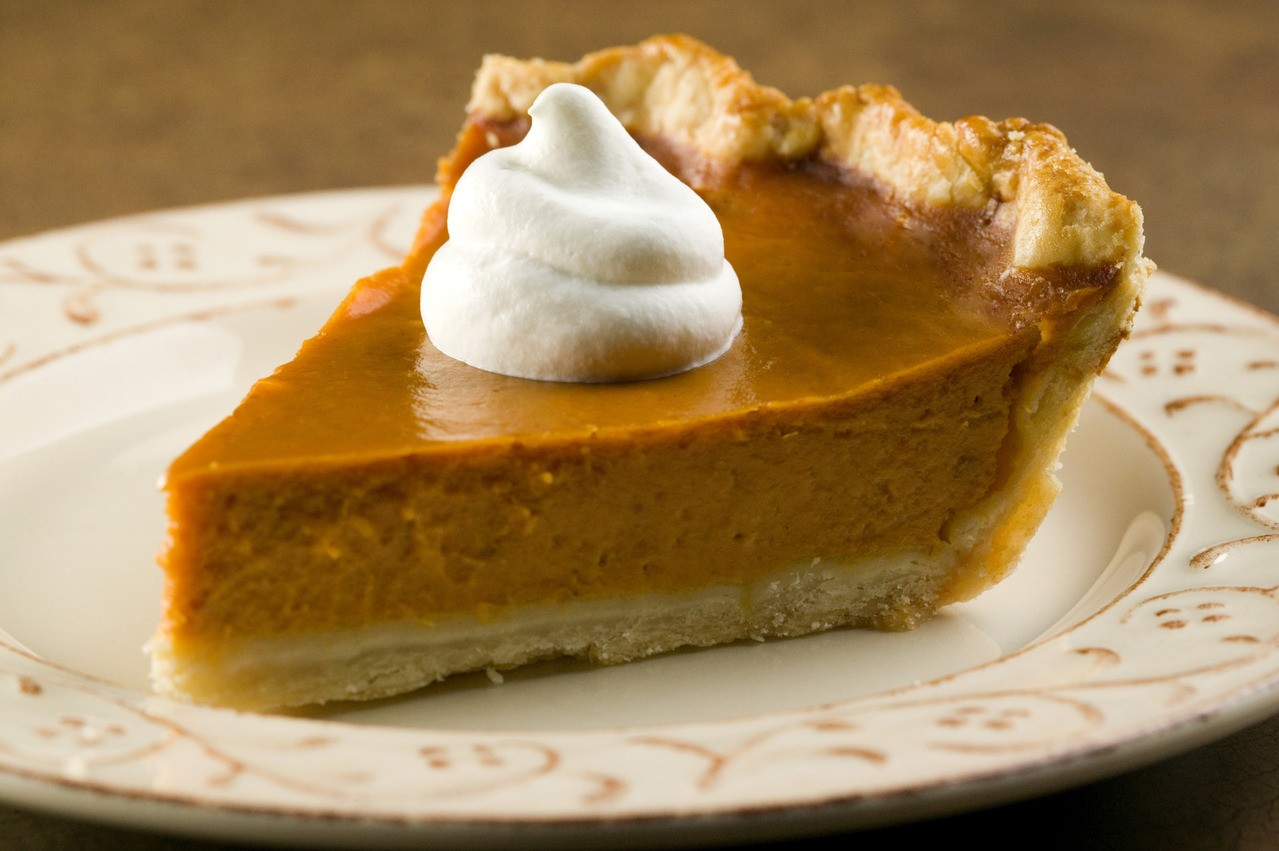 A slice of pumpkin pie sits on a place and has a small dollop of whipped cream on top