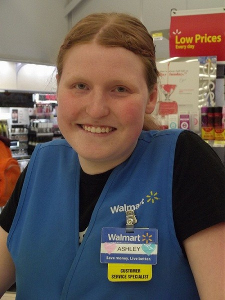 Ashley smiles while standing in the beauty department of a Walmart Canada store with her blue vest and name tag.