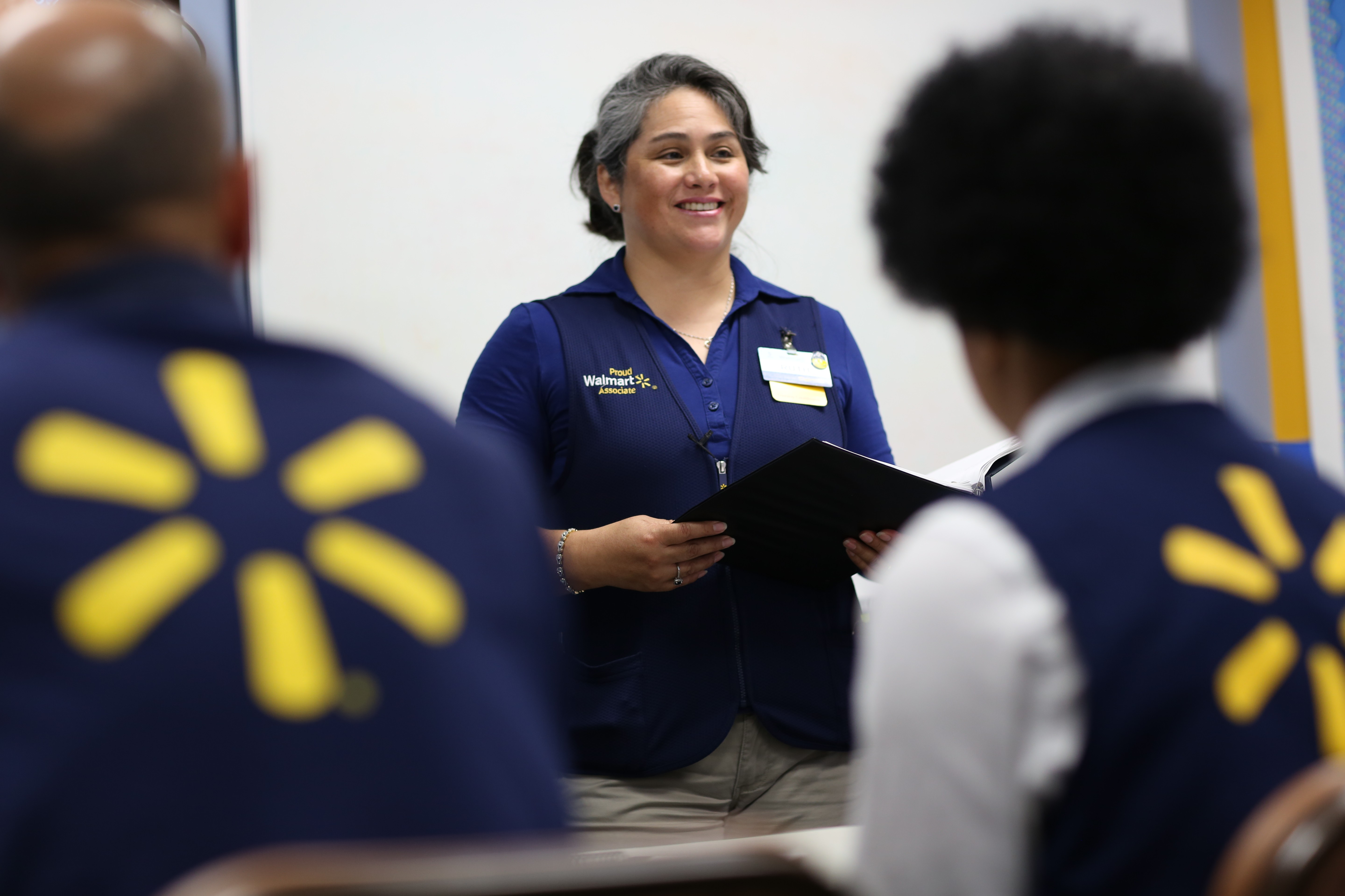 A female associate talking to a group of associates