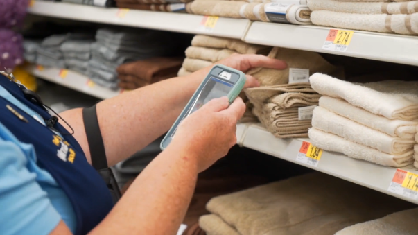An associate scans towels with their phone