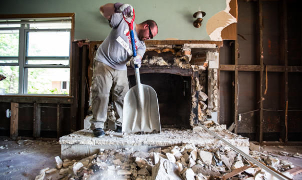 A man from Team Rubicon shovels rubble from a fireplace