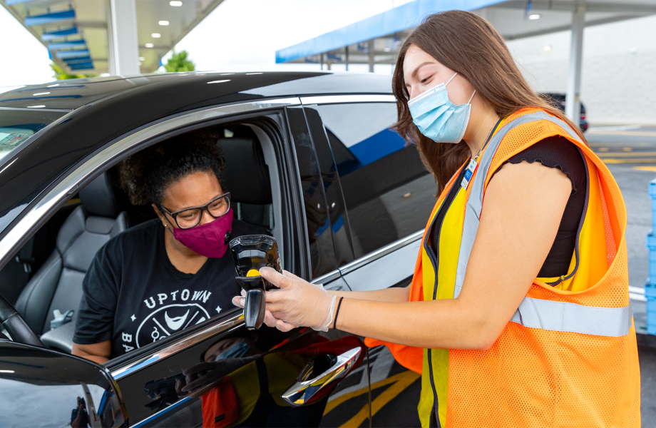 Associate greeting customer with masks in car