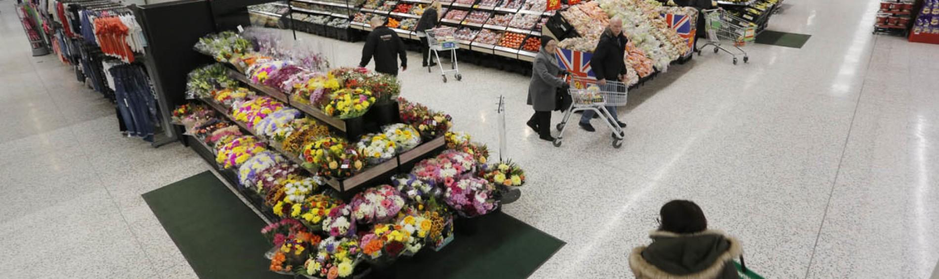 顾客他们的购物车在新鲜农产品和鲜花周围