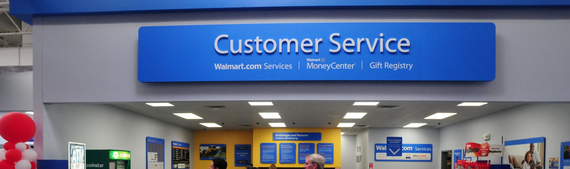 "The Walmart Customer Service center is pictured with three customers walking in front of the area's opening. Walmart banners and signs adorn the walls of the customer service center. A large, blue sign above the area reads ""Customer Service. Walmart.com Services 