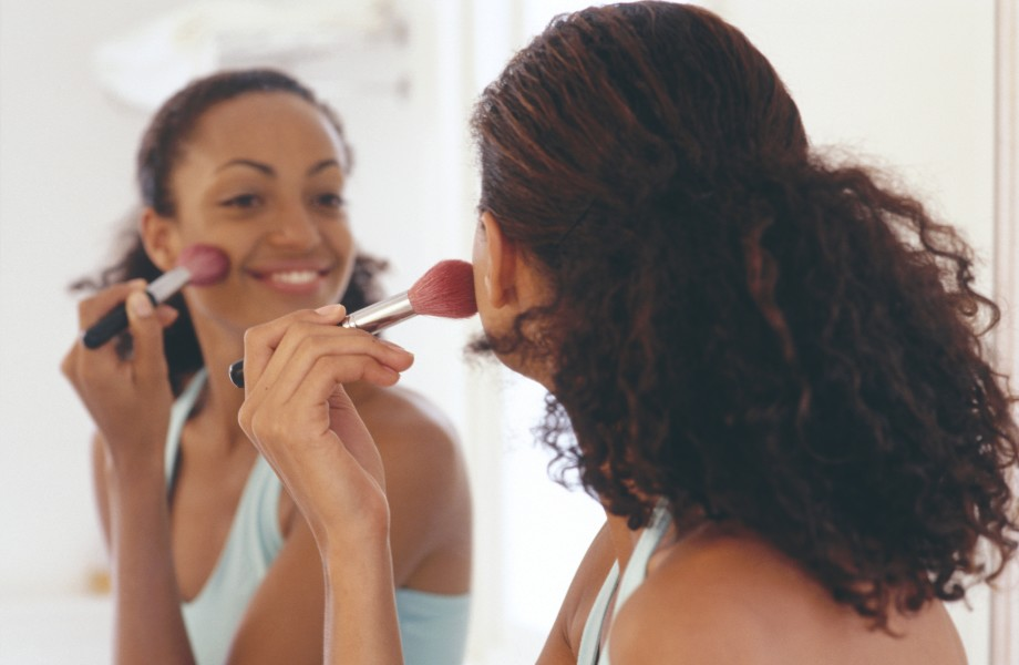 A woman brushes on makeup while looking in a mir