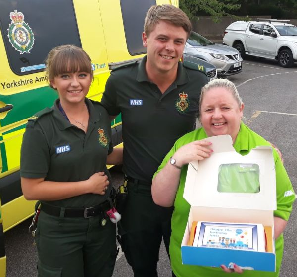 Asda Dewsbury community champion Sharon Kingswood with the NHS birthday cake at Yorkshire Ambulance Service