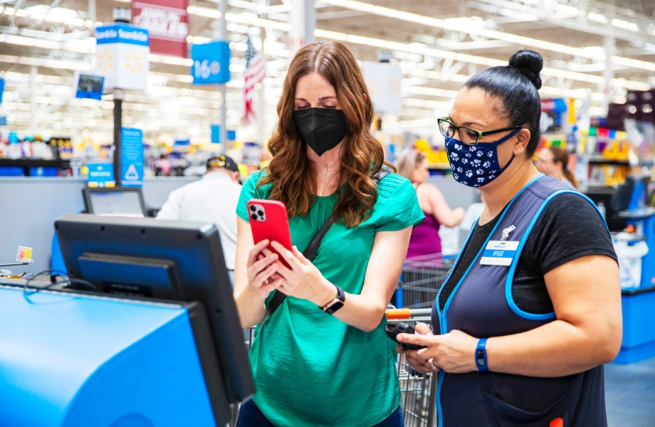 A masked associate helps a customer check out using a mobile device