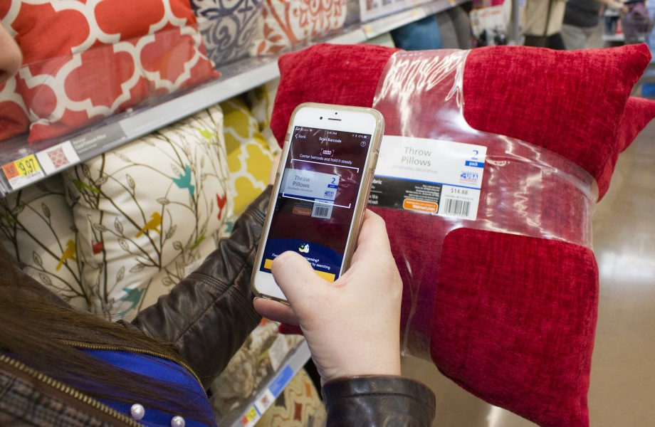 A shopper uses the Scan & Go Express app on her smartphone to scan a bar code on pillows.