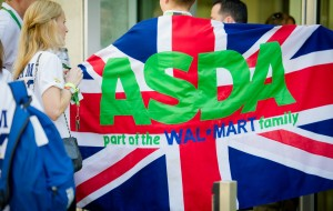 An Asda colleague walks with a UK flag behind him