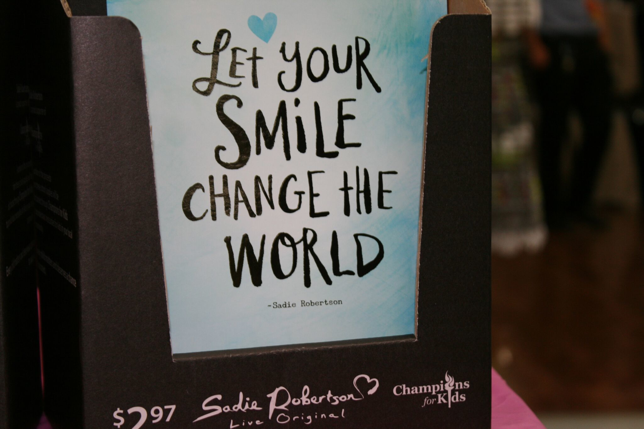"Sadie Robertson product. Book title reads ""Let your smile change the world"""