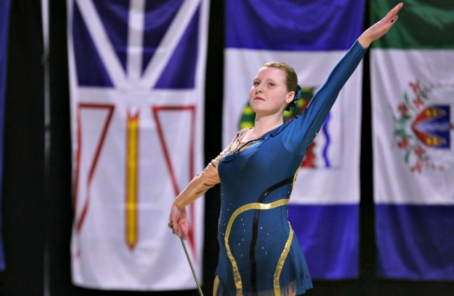 Ashley Wilwand is wearing a blue and gold gymnast outfit and is standing tall during a performance
