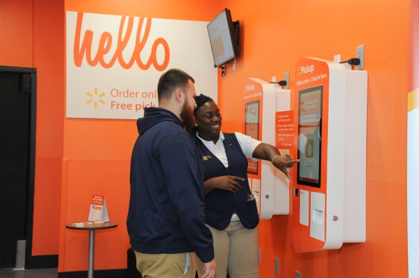 An associate assists a customer at a pickup kiosk